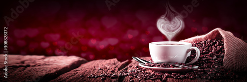 Fotografia, Obraz Coffee With Heart Shaped Steam On Old Weathered Table And Red Heart Bokeh Backg