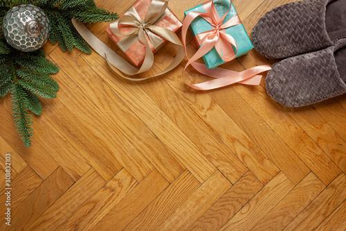 Obraz Boże Narodzenie - tło drewniane, prezenty, kapcie, gałązka jodły, bombka i miejsce na tekst - fototapety do salonu