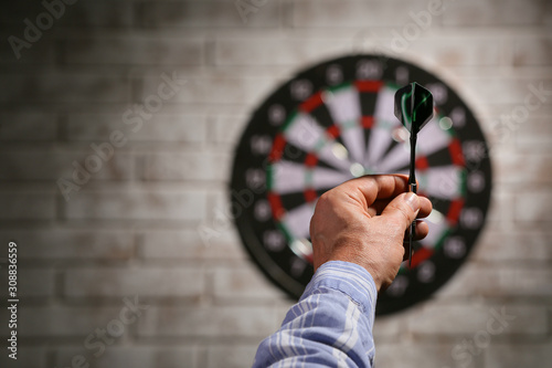 Young man playing darts indoors Wallpaper Mural