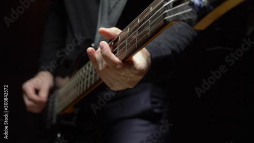 man plays the bass guitar. Dark background. slowmo - 308842572