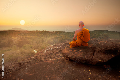 Buddhist monk in meditation at beautiful sunset or sunrise background on high mo Wallpaper Mural