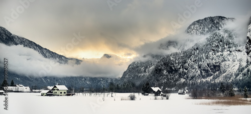 Fotografía Typical view of small alps village from window of train in snowy winter day
