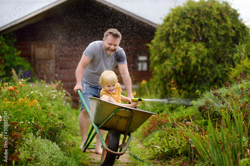 Happy little boy having fun in a wheelbarrow pushing by dad in domestic garden on warm sunny day Poster Mural XXL