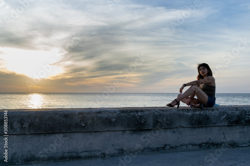 young woman looking the sunset sitting on pier