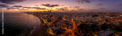 Fototapeta Aerial view of Tel Aviv Yafo along the Mediterranean sea at predawn with colorful sky over the city in Israel obraz