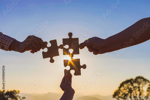 Human hands holding jigsaw puzzle at sunset background Wallpaper Mural