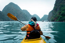 Young Beautiful Woman Floating On A Kayak Between The Rocks Sticking Out Of The Sea. The Girl Rowing The Oars On The Background Of Beautiful Sea Landscape. Water Active Sports.