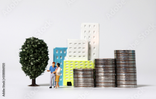 Foto A miniature couple standing in front of a miniature building with a pile of coins