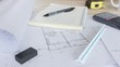 Engineers drawing home on the wood table, Architect design of house placed on wooden table, Male hands draw with a pencil and other drawing tools, Manipulator outline residence, Closeup slider view
