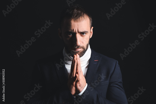 Portrait of praying young man on dark background Canvas Print