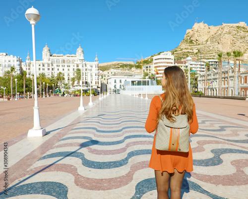 Back view of traveler girl walking in Alicante promenade, Spain.