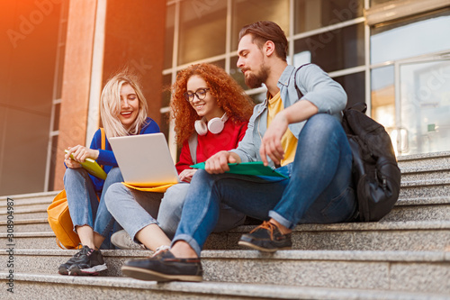Group of friends using laptop outside university