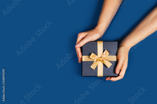 Gift box with surprise in a female hands on classic blue background. Flat lay, top view, place for text.