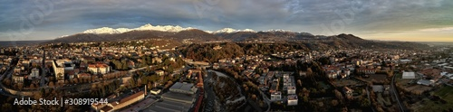 Fototapeta Aerial view of the city of Biella, with snow on the mountains obraz