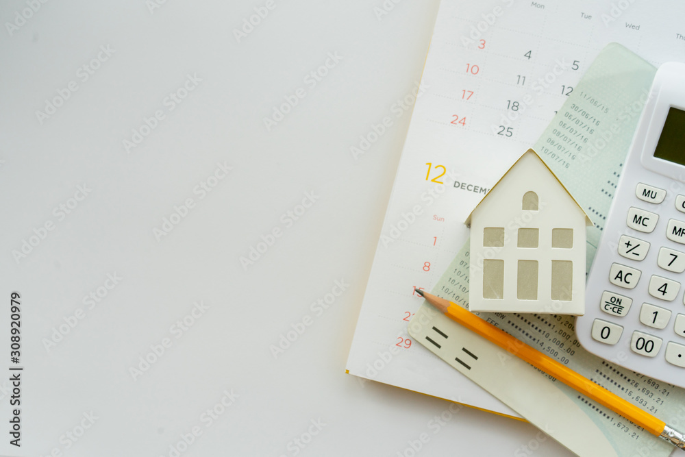 Fototapeta close up top view group of calculator , home model ,yellow pencil, banking account book and calendar on white color background with space for money management ,home loan and personal financial concept