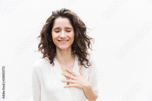Cuadros en Lienzo Happy grateful pretty woman with closed eyes applying hand to chest