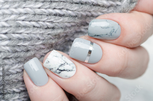 Foto white grey marble manicure with silver stripe on grey background