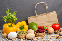 A Set Of Products For Healthy Eating. Paper Bag With Walnuts, Chickpeas, Beans, Lentils, Yellow And Red Peppers, Tomatoes, Avocado On A Gray Background. .
