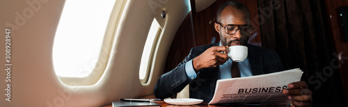 Tablou Canvas panoramic shot of african american businessman in glasses reading business newsp
