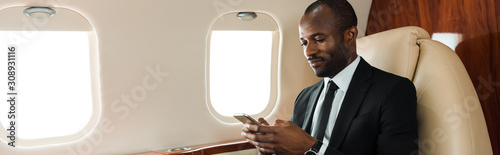 Fototapeta panoramic shot of handsome african american businessman using smartphone in private jet obraz