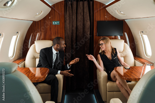 Obraz selective focus of happy african american businessman gesturing near businesswoman in private plane - fototapety do salonu