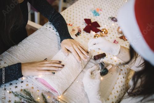 Fotografía  Manicurist pouring white brocade over woman's nails