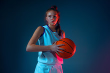 Strength.Young Caucasian Female Basketball Player On Blue Studio Background In Neon Light, Motion And Action. Concept Of Sport, Movement, Energy And Dynamic, Healthy Lifestyle. Posing Confident.