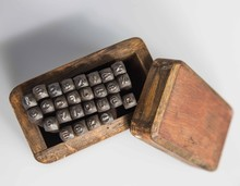 London, England, 29/11/19 Vintage Retro Old School Aged Wooden Box Full Of A Set Of Alphabetical And Numerical Steel Punches Made Of Strong Metal For Industrial Production Shot On White Background