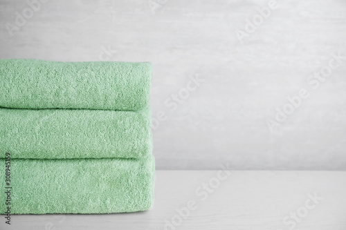 Fotomural Stack of clean bath towels on white wooden table. Space for text