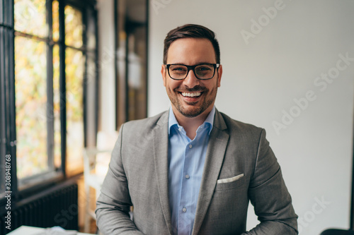 Obraz Portrait of young businessman standing in his off - fototapety do salonu