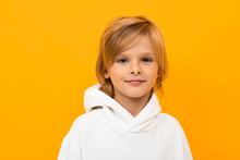 Portrait Of Blond Boy Grimacing On Yellow Studio Background Close-up