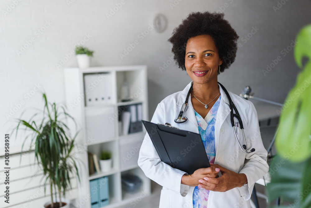 Fototapeta Portrait of female African American doctor standing in her office at clinic