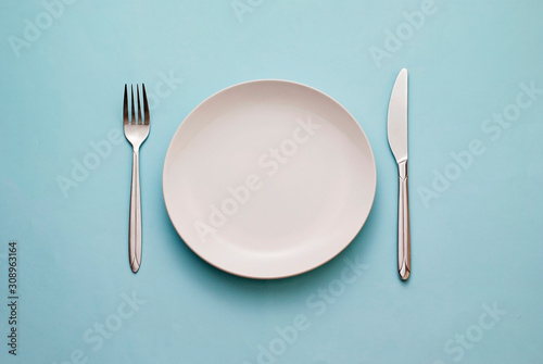 Clean empty white plate with knife and fork Fototapeta