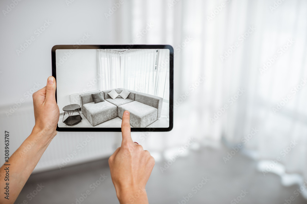 Fototapeta Placing new furniture on a digital tablet into the empty interior, looking how it looks before buying. Concept of augmented reality in design and retail business