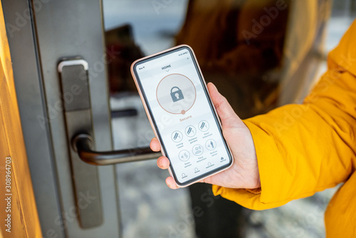 Obraz Locking smartlock on the entrance door using a smart phone remotely. Concept of using smart electronic locks with keyless access - fototapety do salonu
