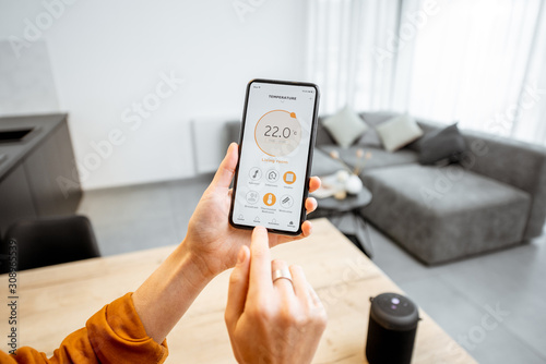 Fototapeta Controlling home heating temperature with a smart home, close-up on phone. Concept of a smart home and mobile application for managing smart devices at home obraz