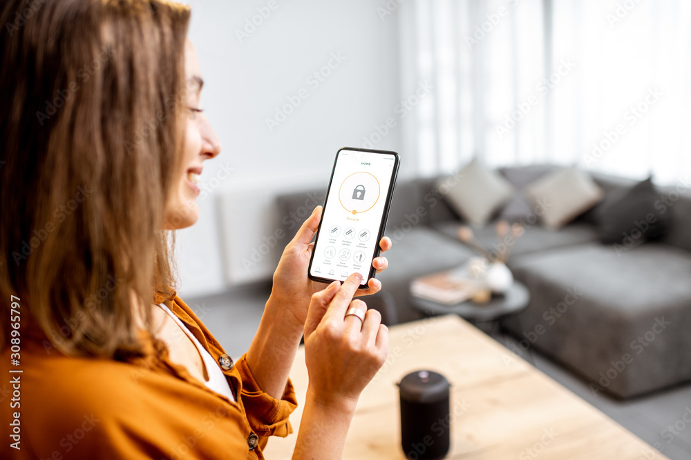 Fototapeta Young woman holding smart phone with launched security application at home. Concept of controlling and managing home security from a mobile device