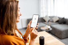 Young Woman Holding Smart Phone With Launched Security Application At Home. Concept Of Controlling And Managing Home Security From A Mobile Device