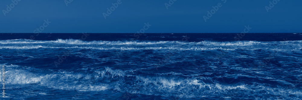 Fototapeta Color of the year 2020 classic blue. Stormy sea and classic blue sky in summer sunny day. Beautiful natural panoramic background with space for text. Fashionable pantone color trend concept, banner