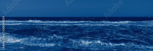 Color of the year 2020 classic blue. Stormy sea and classic blue sky in summer sunny day. Beautiful natural panoramic background with space for text. Fashionable pantone color trend concept, banner