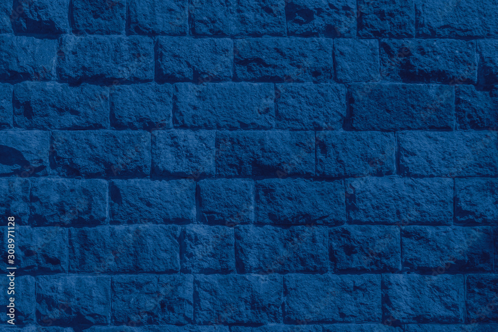 Fototapeta Color of the year 2020 classic blue. Stone brickwork texture of old ancient wall in sunny day. Modern luxury background for design with space for text. Fashionable pantone colour trend concept