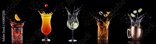 Photo fruit falling into a collection of splashing cocktails isolated on black backgro