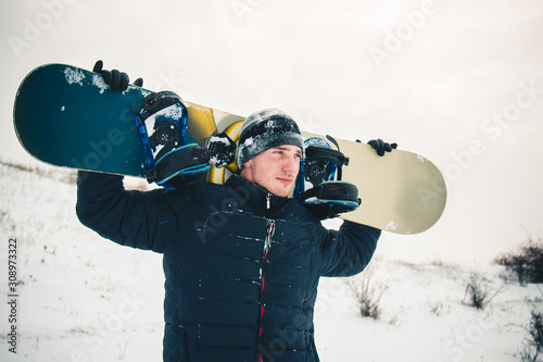 Happy young man with snowboard enjoying sunny weather in snowy mountains Billede på lærred