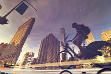 Manhattan In Puddle Reflection With Flatiron Building, Pedestrians, Bicycle, Cloudy Sky