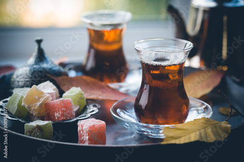 Glass Cup of turkish tea served in traditional style with summer outdore view Canvas Print