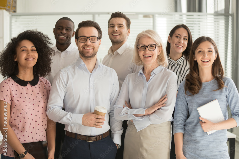 Fototapeta Smiling diverse employees posing for photo in office