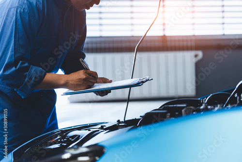 Leinwand Poster Car mechanic holding clipboard and checking to maintenance vehicle by customer claim order in auto repair shop garage