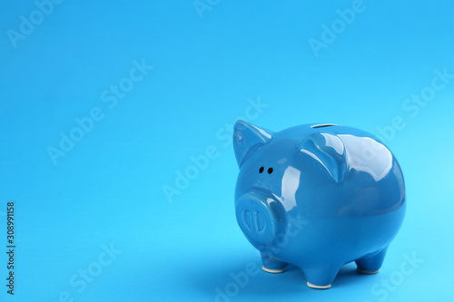 Fotografija Piggy bank on blue background. Space for text