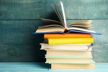 Stack Of Colorful Books On Light Blue Wooden Table