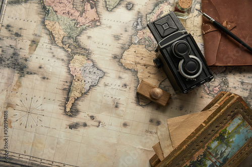 Fototapeta mapa świata   top-view-of-vintage-camera-notepad-with-fountain-pen-stamp-and-painting-on-map-backgroun